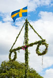 Midsummer. A traditional swedish midsummer pole with a swedish flag Royalty Free Stock Photos