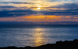 Midsummer night over sea. Scenic view of golden midsummer night over sea with Senja island in foreground, Norway Royalty Free Stock Photos