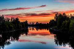 Midsummer night by the river. Vibrant colors reflecting of the river surface Royalty Free Stock Image