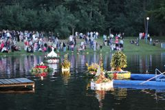 Bonfire, releasing wreaths on water. Midsummer Nights, releasing wreaths on water, bonfire, folk tradition, colorful garlands float on the water, floating Stock Photo