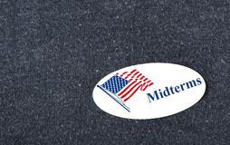 Midterms sticker on shirt. Closeup of a sticker with an American flag and the word `Midterms` placed on a navy shirt stock image