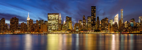 Midtown East skyscrapers from the East River at twilight. New York City. Panoramic view of Midtown East skyscrapers from the East River at twilight. Manhattan Stock Photography
