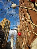 Midtown holiday cityscape. Ornaments on tree branches below Empire State Building. Manhattan morning in December. Red and white globe light ornaments in morning stock photography