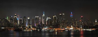 Midtown Manhattan Panorama. New York City Midtown at Night, showing Empire State Building in red and blue, the midtown area, including the glow from Times Square Royalty Free Stock Photos