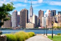The midtown Manhattan skyline in New York City on a beautiful su. The midtown Manhattan skyline in New York City on a summer day as seen from a beautiful park in Royalty Free Stock Photos
