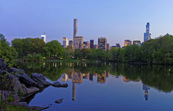 Midtown Manhattan skyline reflected from water in Central Park. Midtown Manhattan skyline reflected from the water in Central Park.  New York, USA. Skyscrapers Royalty Free Stock Photo
