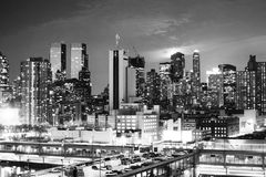 Midtown Manhattan at sunset bw. NEW YORK CITY, USA - MARCH 25 : A view of a parking lot on top of a building and the panorama of Midtown Manhattan at sunset on Stock Photos