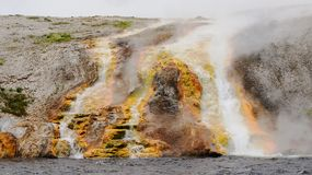 Midway Geyser Basin at Yellowstone National Park. Bacteria and minerals create a colorful scene in the scalding hot run-off water of the Excelsior Geyser Crater Stock Photo