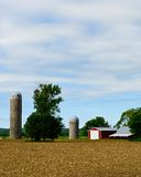 Midwest Farm. Barn, Field and Silos Against a Blue Sky on a Midwestern Farm Royalty Free Stock Photo