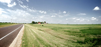 Midwest Scenic Drive. Roadside panoramic image of a Midwestern scenic Route in Summer with highway, blue sky with white puffy clouds and green fields with farm Stock Photos