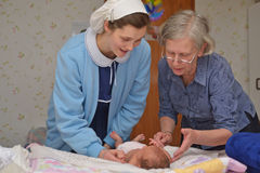 Midwife with baby. A senior midwife checks a newborn baby with her mother Royalty Free Stock Images