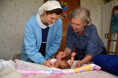 Midwife with baby. A senior midwife checks a newborn baby with her mother Royalty Free Stock Photos