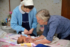 Midwife with baby. A senior midwife checks a newborn baby with her mother Royalty Free Stock Image