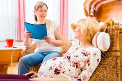 Midwife seeing pregnant mother in practice. Midwife consulting pregnant women for pregnancy and childbearing in practice Royalty Free Stock Photography