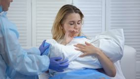 Midwife giving woman crying from happiness newborn child, labor and delivery