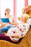 Midwife seeing pregnant mother in practice. Midwife consulting pregnant women for pregnancy and childbearing in practice Royalty Free Stock Image