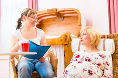 Midwife seeing pregnant mother in practice. Midwife consulting pregnant women for pregnancy and childbearing in practice Stock Photo