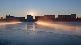Midwinter sunrise on river Oulujoki. Sun rises behind apartment buildings on a cold midwinter morning in Oulu, Finland Royalty Free Stock Photo