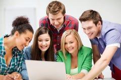 Międzynarodowi ucznie patrzeje laptop przy szkołą Obraz Stock