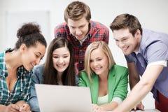 Międzynarodowi ucznie patrzeje laptop przy szkołą Obraz Royalty Free