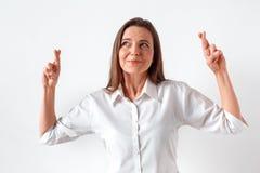 Mieć_nadzieja dla lepszy Kobiety pozycja odizolowywająca na bielu z palcami krzyżującymi zdjęcia royalty free