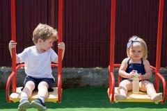 Mieć dobrego czas Włosiany salon dla dzieci Mali dzieci z blondynem na huśtawce Mały brat i siostra cieszymy się fotografia royalty free
