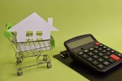 Mieści stawiający w kalkulatorze na biurku i wózku na zakupy Oszczędzania dla domu, kupuje domy, bubli domy, nieruchomość lub bud zdjęcie royalty free
