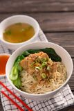 Mie or bakmi ayam. Seasoned yellow wheat noodles topped with diced chicken meat royalty free stock image