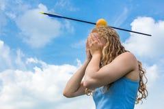 Miedo de la sensación del adolescente con la manzana y la flecha en la cabeza Imágenes de archivo libres de regalías