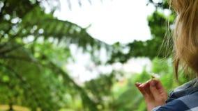 Miedzianowłosa dziewczyna obraca kwiatu w ona przeciw tłu las ręki i śmiechy zbiory