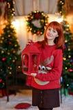 Miedzianowłosa dziewczyna w czerwonym pulowerze z reniferowy ono uśmiecha się i Obrazy Royalty Free