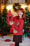 Miedzianowłosa dziewczyna w czerwonym pulowerze z reniferowy ono uśmiecha się i Zdjęcia Stock
