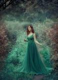 Miedzianowłosa dziewczyna w zieleni, szmaragd, luksusowa suknia w podłoga z długim pociągiem, Princess chodzi w czarodziejce obrazy stock