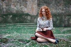 Miedzianowłosa dziewczyna z książkowym obsiadaniem w parku na trawie Obraz Stock