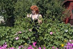 Miedzianowłosa kobieta podczas gdy pracujący w jej ogródzie Zdjęcia Stock