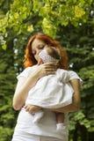 Miedzianowłosa kobieta z jej dzieckiem w parku fotografia stock