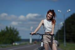 Miedzianowłosa młoda dziewczyna w skrótach i wierzchołkach pozuje stać z bicyklem zdjęcie stock
