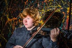 Miedzianowłosa piegowata chłopiec bawić się skrzypce z różnymi emocjami o zdjęcia royalty free
