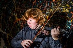 Miedzianowłosa piegowata chłopiec bawić się skrzypce z różnymi emocjami o obraz stock