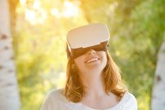 Miedzianowłosa uśmiechnięta dziewczyna w rzeczywistość wirtualna hełmie Zdjęcia Stock