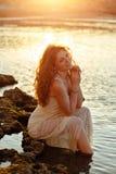 Miedzianowłosa zmysłowa dziewczyna w biel sukni obsiadaniu na skałach Zdjęcie Royalty Free