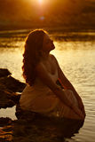 Miedzianowłosa zmysłowa dziewczyna w biel sukni obsiadaniu na skałach Obraz Stock