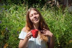 Miedzianowłosi dziewczyna chwyty w jej ręce czerwony kubek z herbatą na tle zielona trawa w lecie obraz royalty free