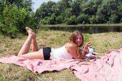 Miedzianowłosy dziewczyny lying on the beach na różowym bedspread na bankach rzeka na słonecznym dniu obraz royalty free
