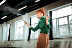 Miedzianowłosy fachowy joga instruktor słucha muzyka z włosianą babeczką fotografia stock