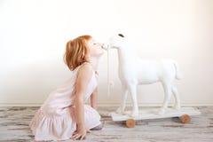 Miedzianowłosych dziewczyna buziaków zabawkarski koń Obraz Royalty Free