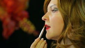 Miedzianow?osa aktorka w przebieralni robi wargi makeup czerwona glosa przygotowywa i?? na scenie zbiory