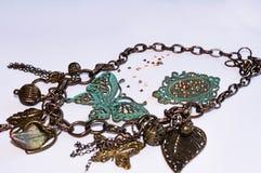 Miedziany łańcuch z dekoracyjnymi motylami, liśćmi, kwiatami i koralikami, fotografia stock
