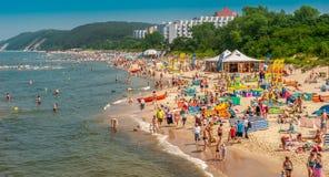Miedzyzdroje/Polen - 07 11 2011: Viele Leute auf dem sandigen Strand ein Sonnenbad nehmend, schwimmend im Meer und entspannen sic Stockfoto