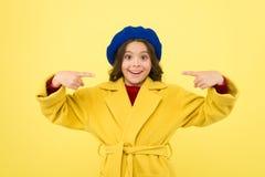 Miejsce dla reklamy reklamy Dziecko promuje coś żółty tło Dziewczyna wskazuje palce wskazujących obraz stock